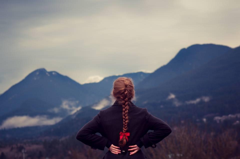 Девушка с косичкой и красным бантом, которая отдыхая в горах, думает про то, как эффективно выполнять свою работу
