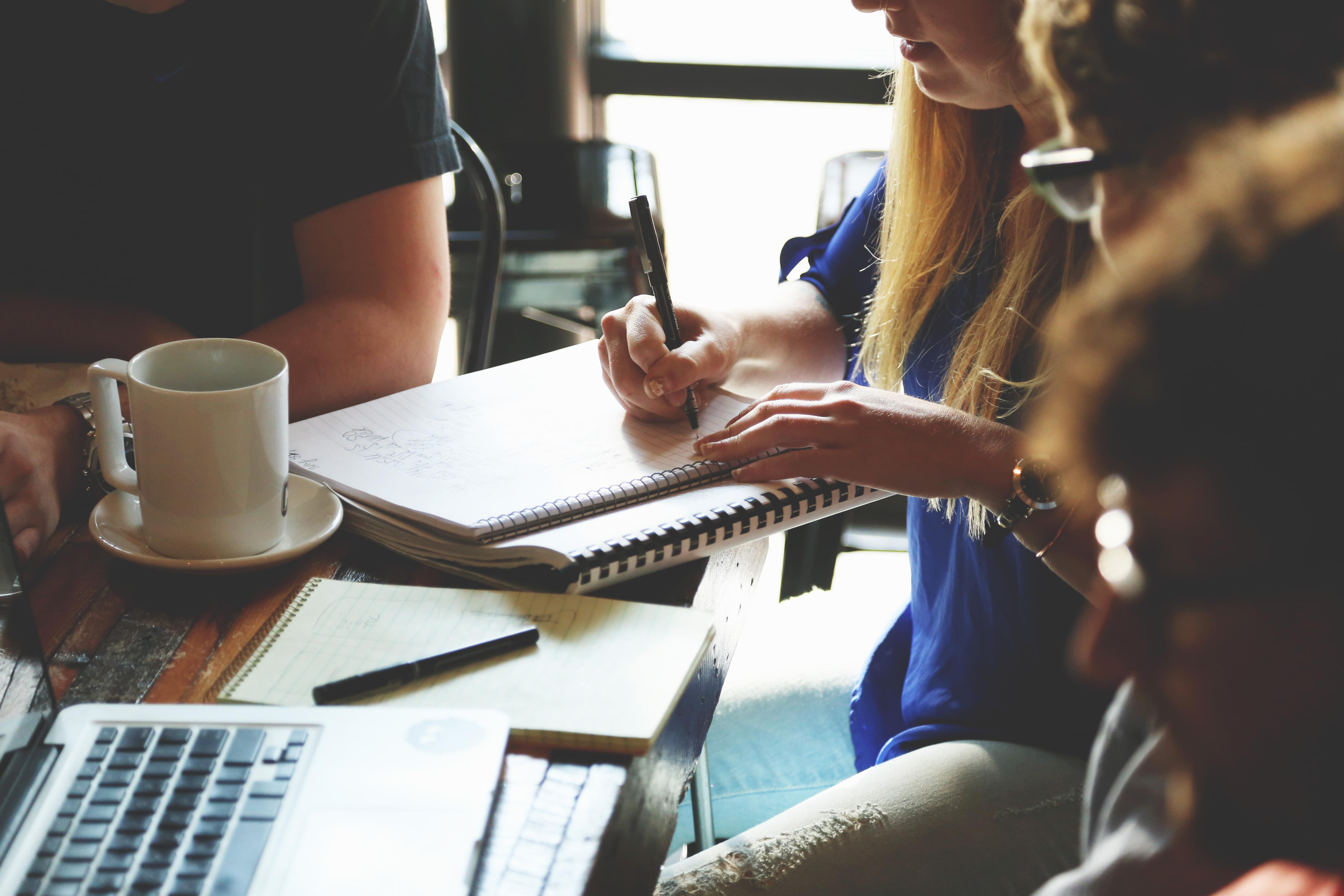 Встреча специалистов, которые записывают в тетради и обсуждают способы реактивации неактивных подписчиков
