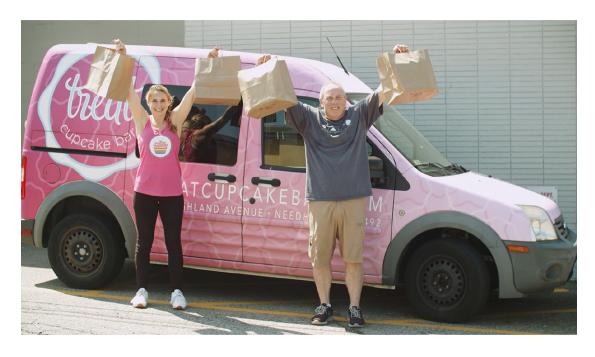 улыбающаяся пара с поднятыми вверх руками на фоне розового автомобиля