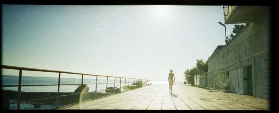 девушка, которая гуляет сама по набережной возле море в солнечный день