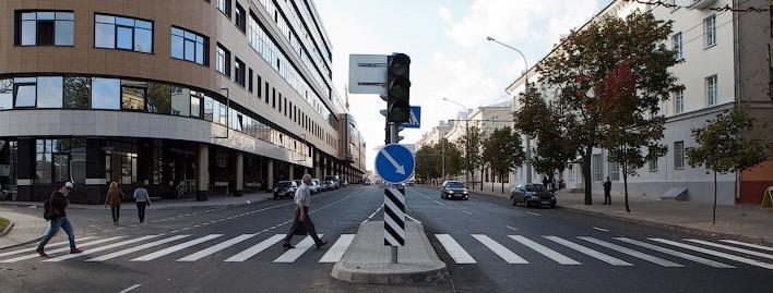 Улица города с пешеходным переходом, несколькими пешеходами и машинами
