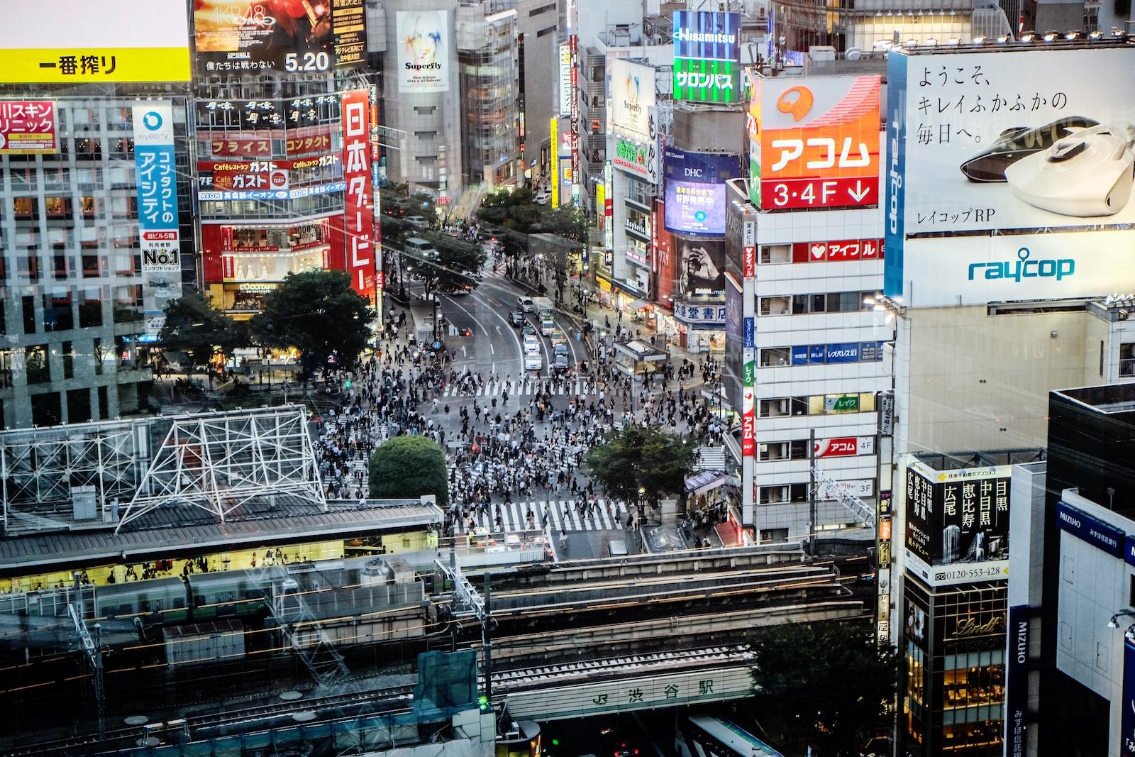 Улица японского города с большим количеством рекламы и толпой людей
