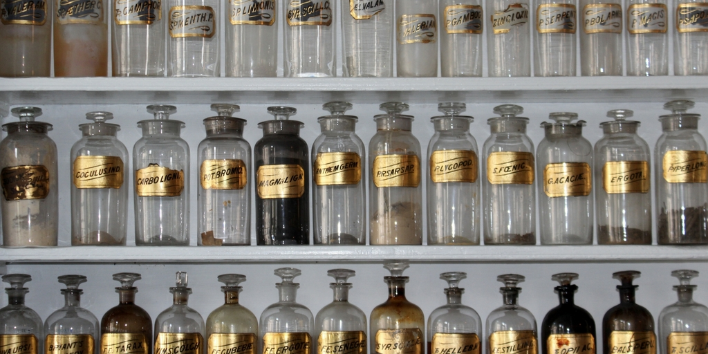 Прозрачные медицинские емкости частично наполненные, которые стоят на полках
