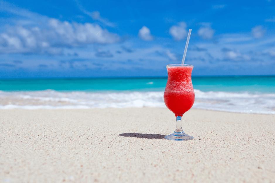 Бокал с коктелем красного цвета и соломкой на берегу моря в солнечный день