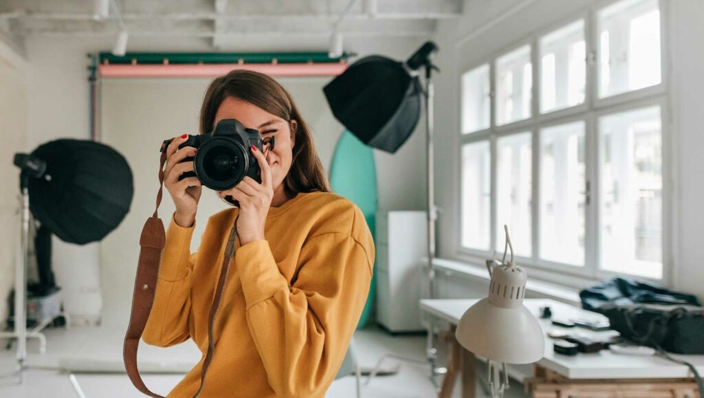 Девушка фотограф с фотоаппаратом в руках